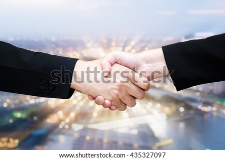 Close-up of business people handshaking in blurred bokeh background of citiscabe nightlife /teamwork - stock photo