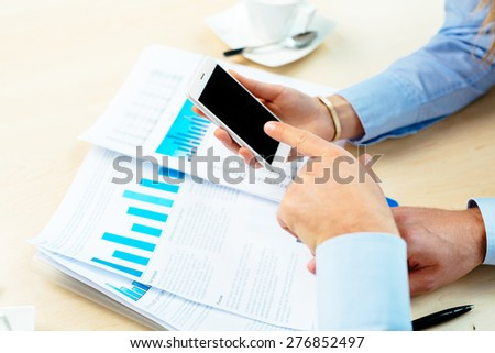 Close-up of business people holding and touching a smartphone - stock photo
