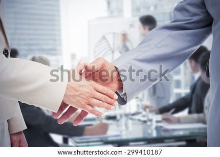 Close up of business people shaking their hands against business people in office at presentation - stock photo