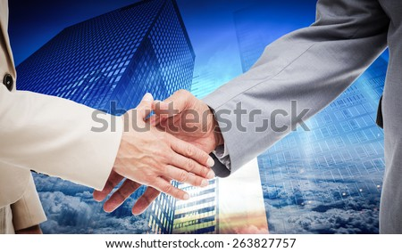 Close up of business people shaking their hands against low angle view of skyscrapers at sunset - stock photo