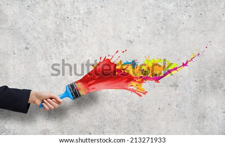 Close up of business person hand holding paint brush - stock photo