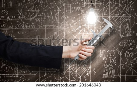 Close up of business person hand measuring bulb - stock photo