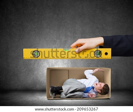 Close up of business person hand measuring man in carton box - stock photo
