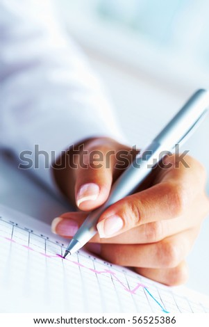 Close-up of business person hand with pen over paper - stock photo