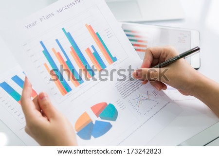 Close-up of  business person using digital tablet with financial diagram - stock photo