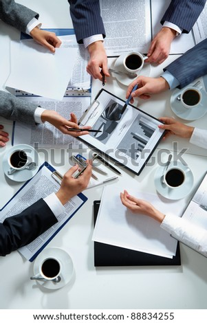 Close-up of business team hands over papers during discussion of a new project - stock photo
