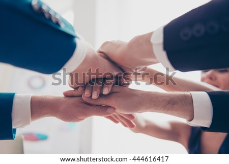 Close-up of business team in formalwear putting their hands on top of each other - stock photo