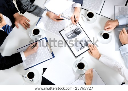 Close-up of business team sitting at the table and discussing a new project - stock photo