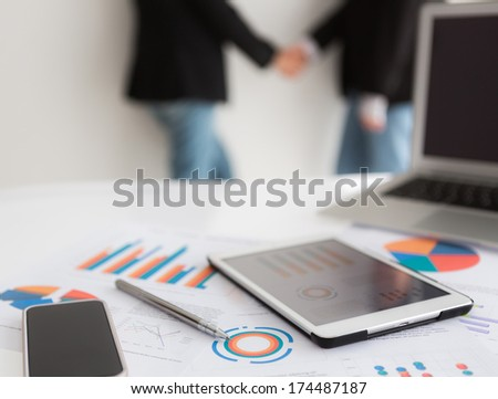 Close-up of business team using digital tablet with financial diagram - stock photo