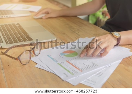 Close-up of Business woman hands pointing at turnover graph while discussing it on wooden desk in office. Vintage filter effect. - stock photo