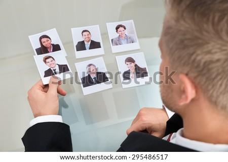 Close-up Of Businessman Choosing Candidate In Office - stock photo