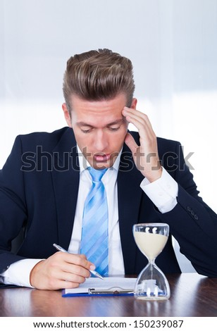 Close-up Of Businessman Filling Form With Hourglass On Desk - stock photo