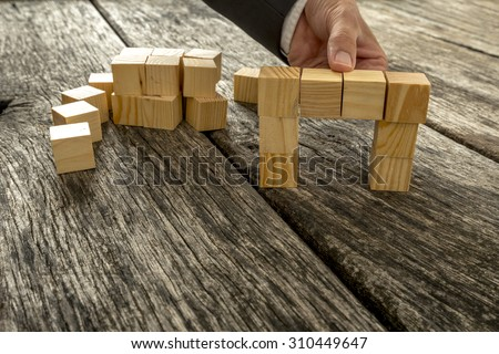 Close up of businessman forming a bridge of small wooden blocks on textured oak desk as he comes to a solution, finding or answer in a conceptual image. - stock photo