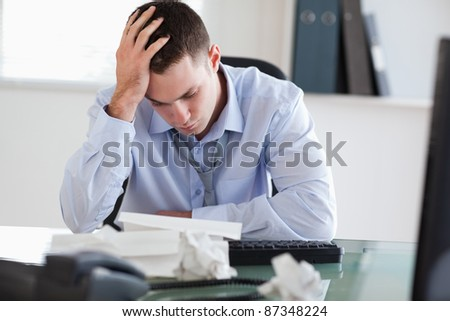 Close up of businessman getting frustrated with paperwork - stock photo
