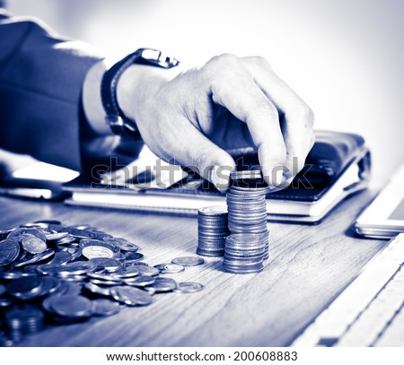 Close-up Of Businessman Hand Count and Put Money Coins To Stack Of Coins with tablet and credit card on wood background - stock photo