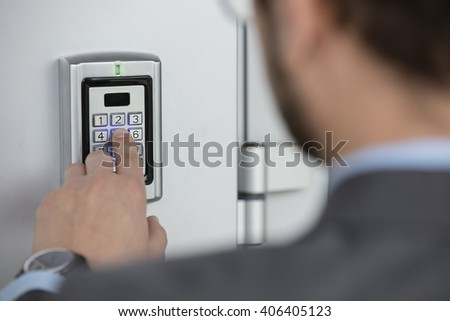 Close up of businessman hand entering security system code - stock photo