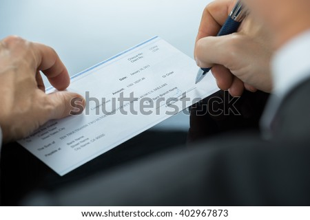 Close-up Of Businessman Hand Filling Blank Cheque At Desk - stock photo