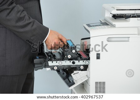 Close Up Of Businessman Hand Fixing Cartridge In Printer Machine At Office - stock photo