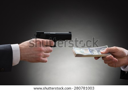 Close-up Of Businessman Hand Giving Money To The Businessperson With Gun - stock photo