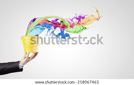 Close up of businessman hand holding bucket with paint - stock photo