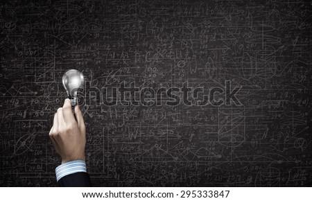 Close up of businessman hand holding glass light bulb - stock photo