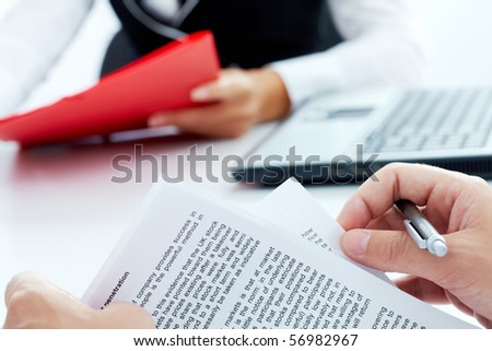 Close-up of businessman hand holding papers and pen - stock photo
