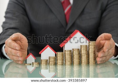 Close-up Of Businessman Hand Near Different Size Houses And Stacks Of Coins On Table - stock photo