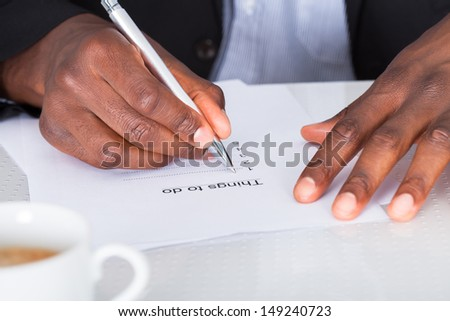 Close-up Of Businessman Hand Planning To Do List - stock photo