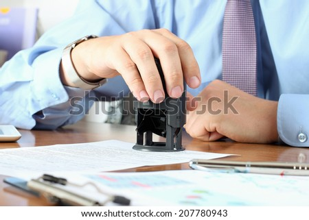 Close-up Of Businessman Hand Pressing a  Stamp On Document in the office  - stock photo