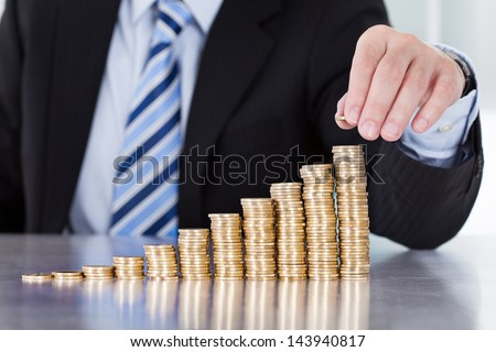 Close-up Of Businessman Hand Put Coins To Stack Of Coins - stock photo