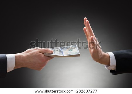 Close-up Of Businessman Hand Rejecting The Money Offered By Other Businessman - stock photo