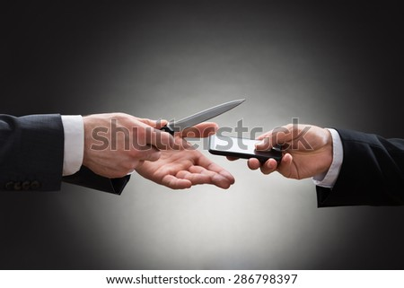Close-up Of Businessman Hand Showing Knife To The Businessperson With Mobile Phone - stock photo