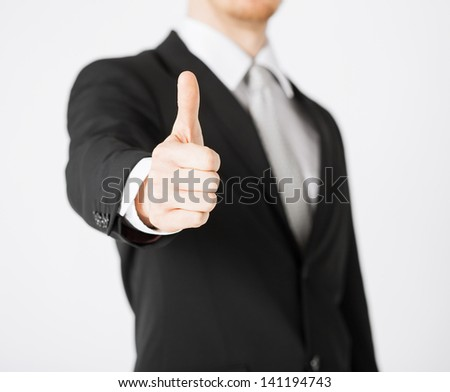 close up of businessman hand showing thumbs up - stock photo