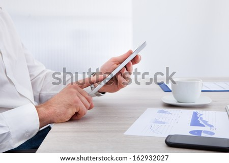 Close-up Of Businessman Hand Using Digital Tablet At Desk - stock photo