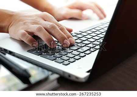 Close up of businessman hand working on laptop computer on wooden desk as concept - stock photo