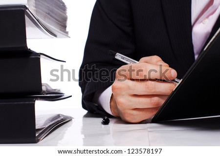 Close up of businessman hand writing with some folders on a table - stock photo