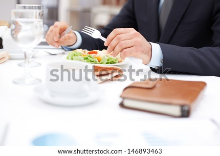 Close-up of businessman hands holding knife and fork over vegetable salad during business lunch - stock photo