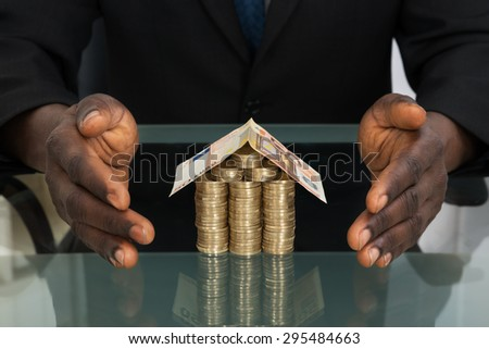 Close-up Of Businessman Hands Protecting House Made Of Money - stock photo