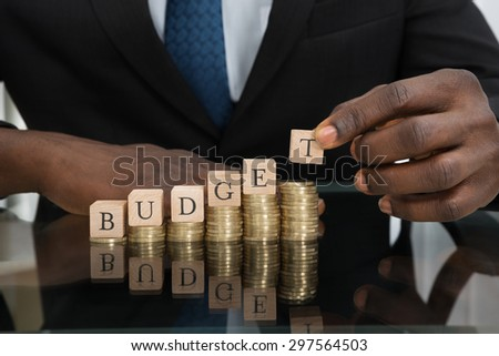 Close-up Of Businessman Hands Putting The Letters Of The Word Budget On Stack Of Coins - stock photo