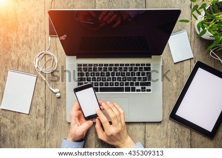 Close-up of businessman hands working on modern electronic devices. Aerial view of modern office interior - stock photo