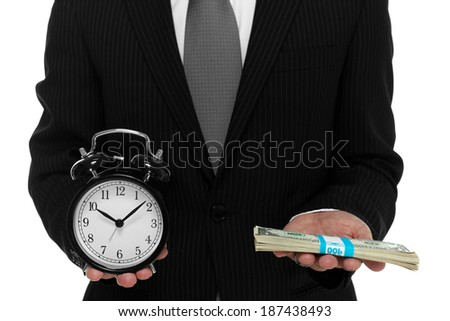 Close up of businessman holding a clock and one stack of cash in hand - stock photo