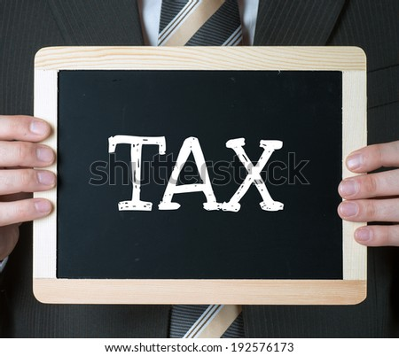 Close up of businessman holding frame with drawn text TAX - stock photo
