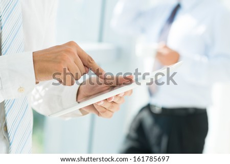 Close-up of businessman holding touchpad and pointing at its screen - stock photo