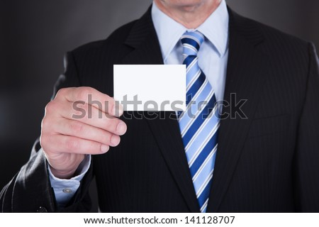 Close-up Of Businessman Holding Visiting Card Over Black Background - stock photo