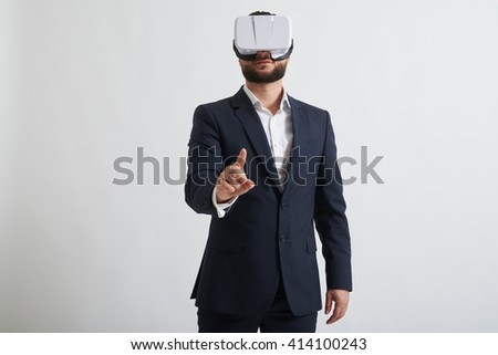 Close up of businessman in a formal wear and virtual reality glasses who trying to touch something with his hand - stock photo
