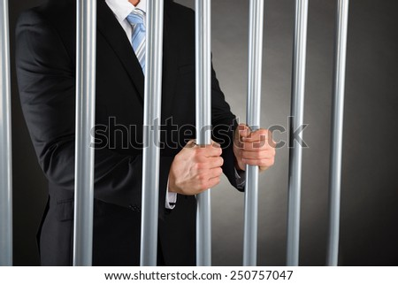 Close-up Of Businessman In Jail Holding Metal Bars - stock photo
