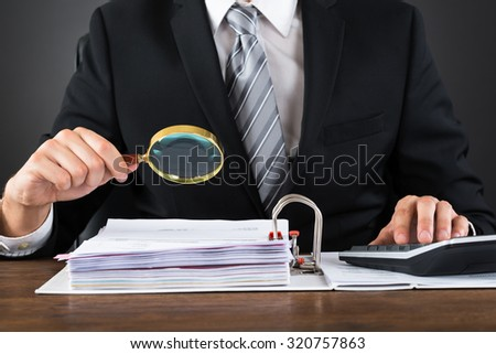 Close-up Of Businessman Inspecting Invoice With Magnifying Glass At Wooden Desk - stock photo