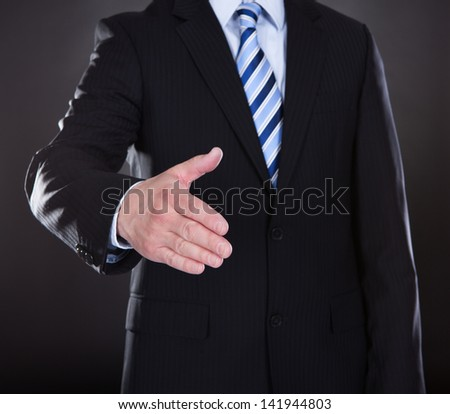 Close-up Of Businessman Offering Handshake Over Black Background - stock photo