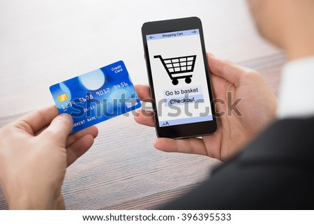 Close-up Of Businessman Paying With Credit Card On Mobile Phone - stock photo