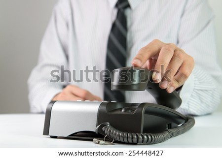 Close up of businessman picking up landline phone - stock photo
